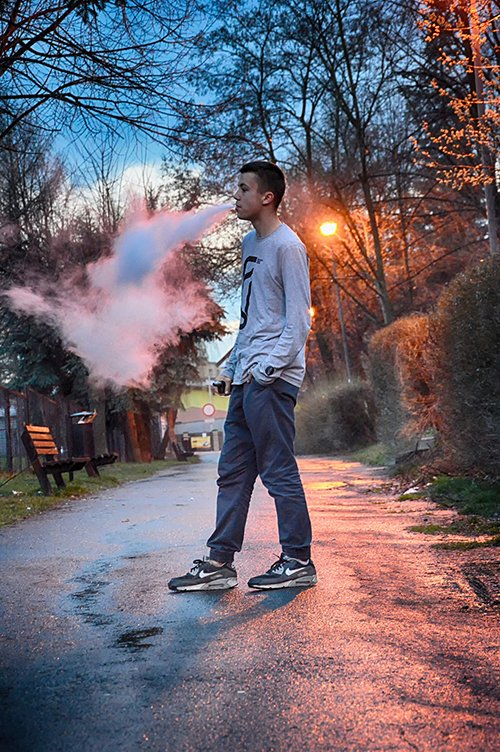 young Caucasian male teen stands in street at twilight blowing big clouds of vape smoke out of his mouth shows one of 10 signs your teen may be vaping