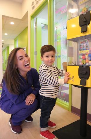 inside pediatric dental office near Solon, Ohio shows Dr. Rachel Rosen with boy getting toy tower prize