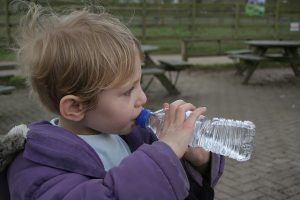 child drinks water for cavity prevention after eating Halloween candy per advice of pediatric dentist Dr. Rachel Rosen
