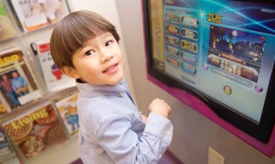 little boy looks up at camera while playing at touchscreen video games inside Great Beginnings Pediatric Dentistry in Twinsburg, Ohio