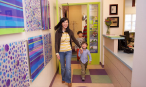 Asian mom walks in Great Beginnings Pediatric Dentistry while holding boy's hand