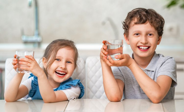 boy and girl sit smiling holding glasses of water demonstrating understanding fluoride benefits and risks includes knowing your water supply information to share with pediatric dentist